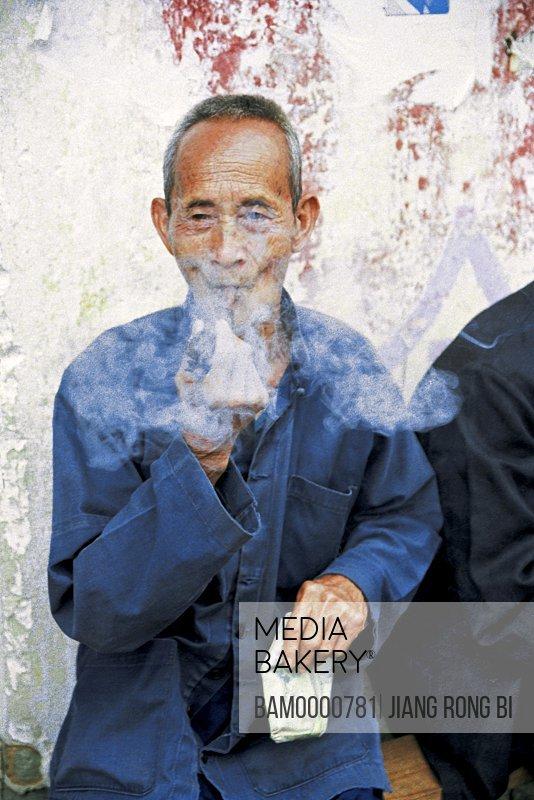 Old man smoking pipe, Yangshuo County, Guilin City, Guangxi Zhuang Nationality Autonomous Region of People's Republic of China