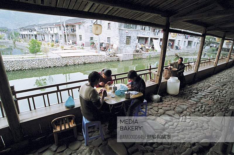 View of people sitting by lake, Residents of Ancient Lishui Village, Nanxi River, Yongjia County, Zhejiang Province, People's Republic of China