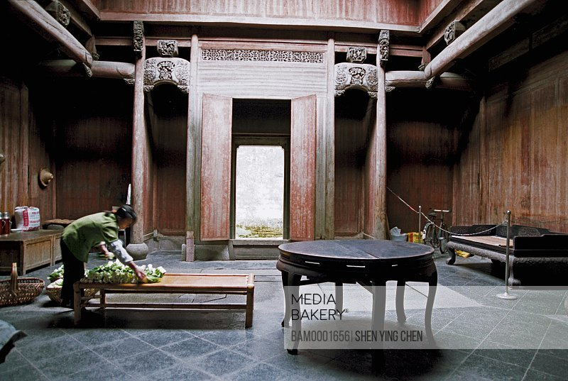 Woman arranging vegetables on table, The Lu Village's peasants of Ming and Qing dynasty's ancient common people residenc exposes vegetable to the sun , Lu Village, Yi County, Anhui Province of People's Republic of China