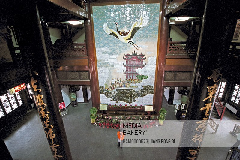 Elevated view of a person standing by ceramic mural of the Huanghe Building bottom hall, Wuhan City, Hubei Province of People's Republic of China