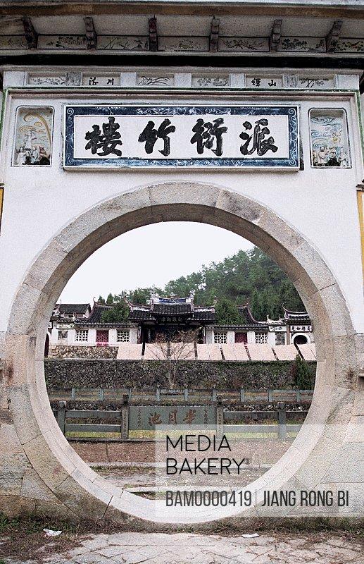"""View of houses through circular wall, Bao's Memorial Temple Inscribed with """"Pai Yan Zhu Lou"""", Taishun County, Zhejiang Province, People's Republic of China"""