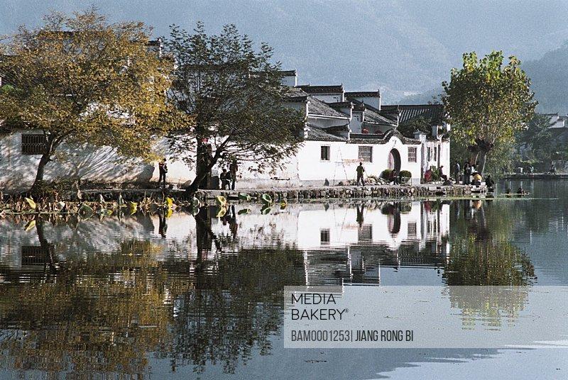 View of people standing beside lake, Nanhu Lake in Hongcun Village, Yixian County, Anhui Province, PRC