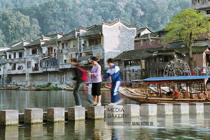 People walking over bridge amid river, The historic bridge of Tuo River, Fenghuang, Xiangxi Prefecture, Hunan Province, People's Republic of China