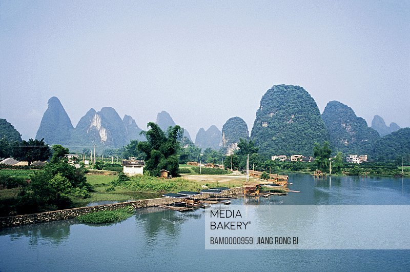 View of rafts on the river with mountains in the background, The scenery of Yulong river, Yangshuo, Yangshuo County, Guilin City, Guangxi Zhuang Nationality Autonomous Region of People's Republic of China