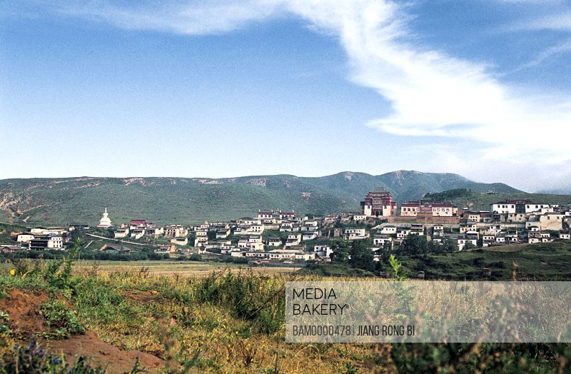 View of houses with mountains in the background, Panorama of Gedan Songzanlin Lamasery, Shangri-la County, Diqing Prefecture, Yunnan Province, People's Republic of China