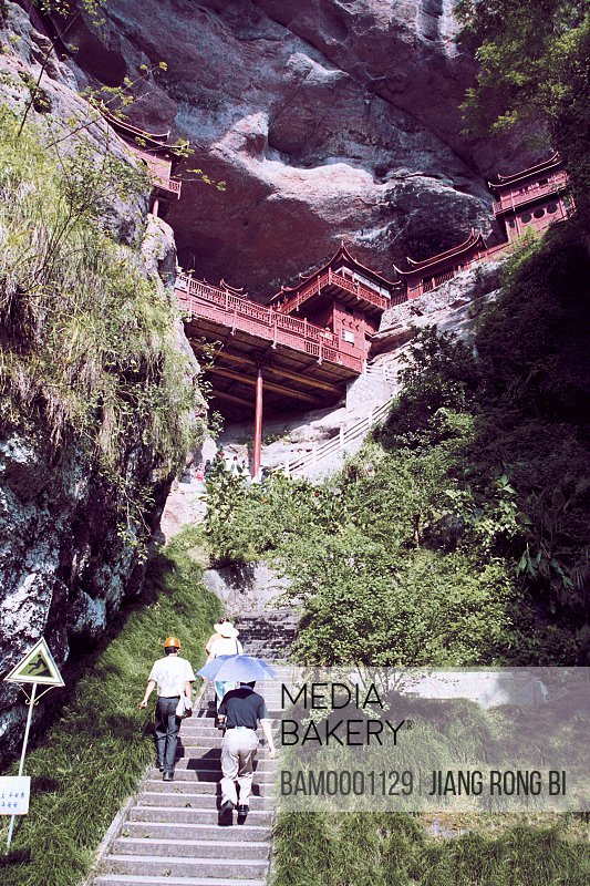 Low angle view of tourists visiting structure built on rocks, Ganlu Temple beside Dajin Lake, Taining County, Sanming City, Fujian Province, PRC