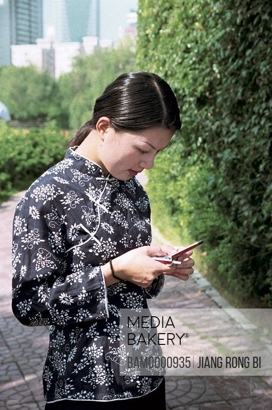 Young woman holding mobile phone, She minority women at the photographic exhibition often Taiwan strait, Fuzhou City, Fujian Province, People's Republic of China