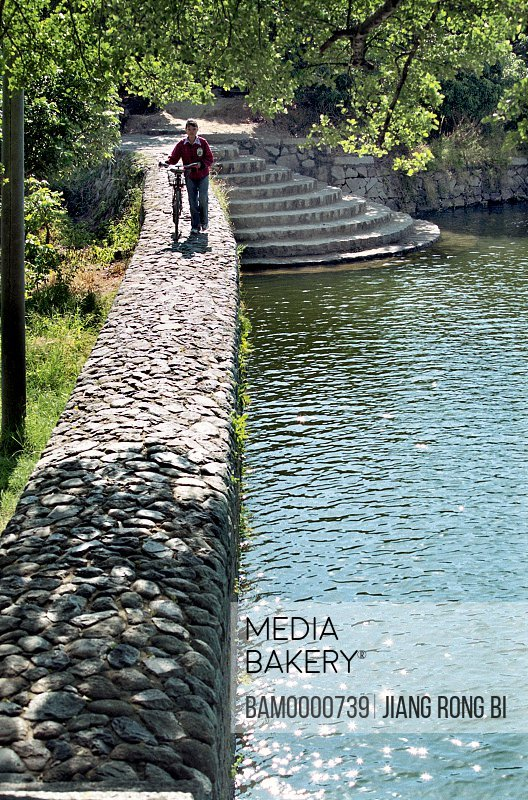 View of girl with bicycle walking on stone-laid riverbank, Stone-laid Riverbank of Yanshou Rivulet in Yanshou Village, Chengxian District, Putian City, Fujian Province, People's Republic of China