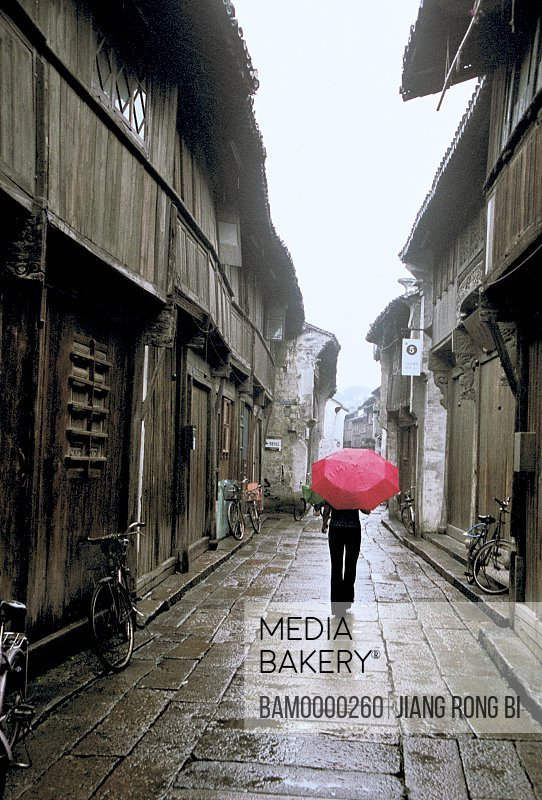 Person walking with umbrella on wet street, Ancient street of Wu town in the rain, Wu Town, Tongxiang City, Zhejiang Province, People's Republic of China
