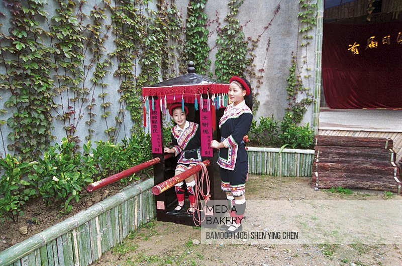 View of young women standing by palanquin, She race character and style of Bainanlanfu, Rixi Township, Jingan Disatrict, Fuzhou City, Fujiang Province of People's Republic of China