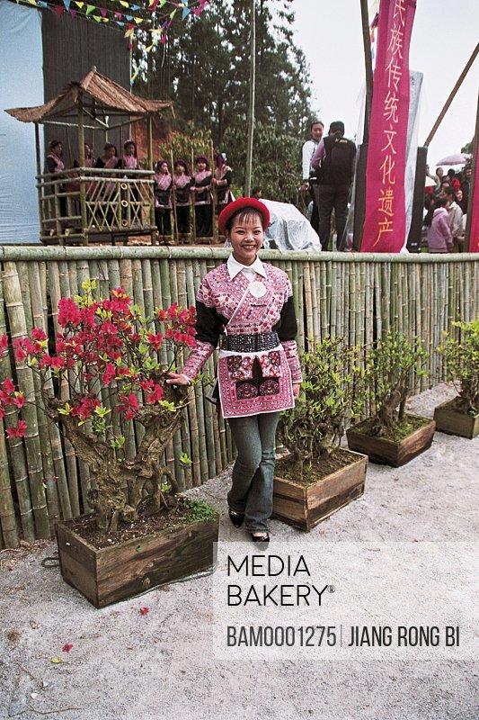 View of young woman standing by potted plants, She Nationality Ladies from Huokou Township , Huokou Township, Luoyuan County, Fuzhou City, Fujian Province, PRC