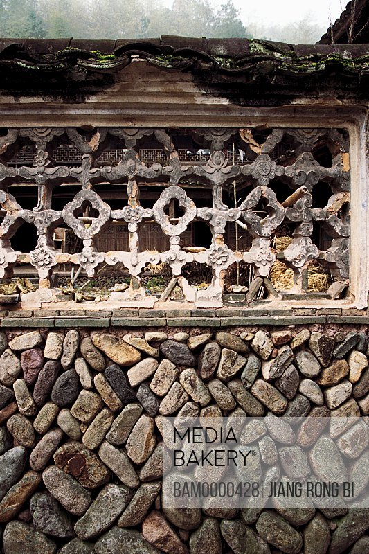 View of a window with latticework on a stonewall, Paper-cut for Decoration of Window in Stone Wall of Ancient House, Taishun County, Zhejiang Province, People's Republic of China
