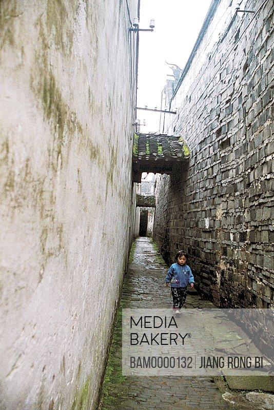 Girl walking in a passageway, The small street of Tongli region of rivers and lakes pond, Tongli Town, Wujiang City, Jiangsu Province of People's Republic of China