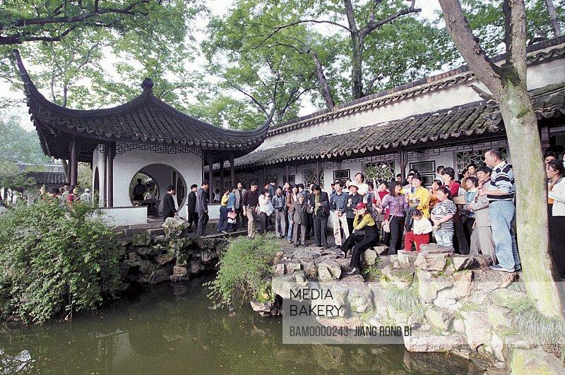 Tourists standing near house by pond, Crowded-visitor's Zhuozheng park, Suzhou City, Jiangsu Province, People's Republic of China