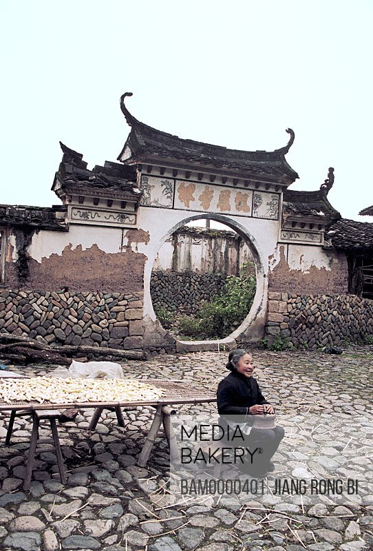 Senior woman sitting on bench with circular entranceway in the background, Ancient Residence in Taishun, Taishun County, Zhejiang Province, People's Republic of China