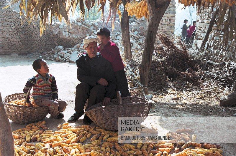 Boy whispering to grandpa, Yichuan County, Yan'an City, Shanxi Province, PRC