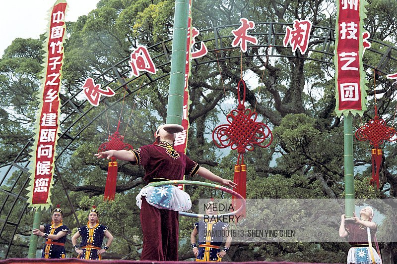 Low angle view of performers balancing poles during a festival, Winter jasmine folk art performance in country forest park, Fuzhou City, Fujian Province of People's Republic of China