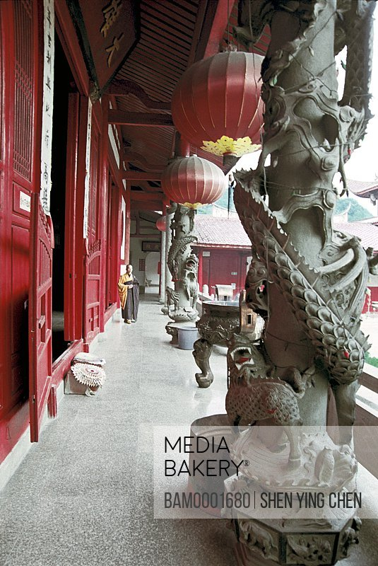 Monk standing in temple pavement with Chinese lanterns hanging, The buddhist priest chants scripture in Linyang temple, Linyang Temple, Lingtou Township, Fuzhou City, Fujian Province of People's Republic of China