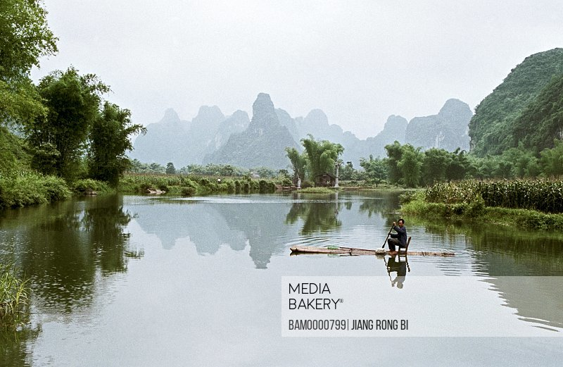 Man crossing river on raft with view of mountains in the background, The scenery of Minsi countryside in Detian, Daxin County, Nanning City, Guangxi Zhuang Nationality Autonomous Region of People's Republic of China