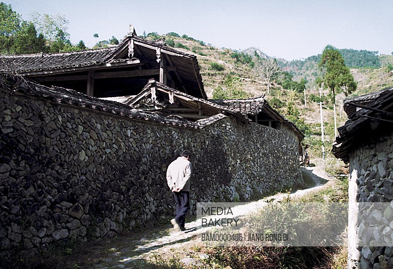 Man walking on pathway by wall, Stone Wall of Ancient Residence, Taishun County, Zhejiang Province, People's Republic of China