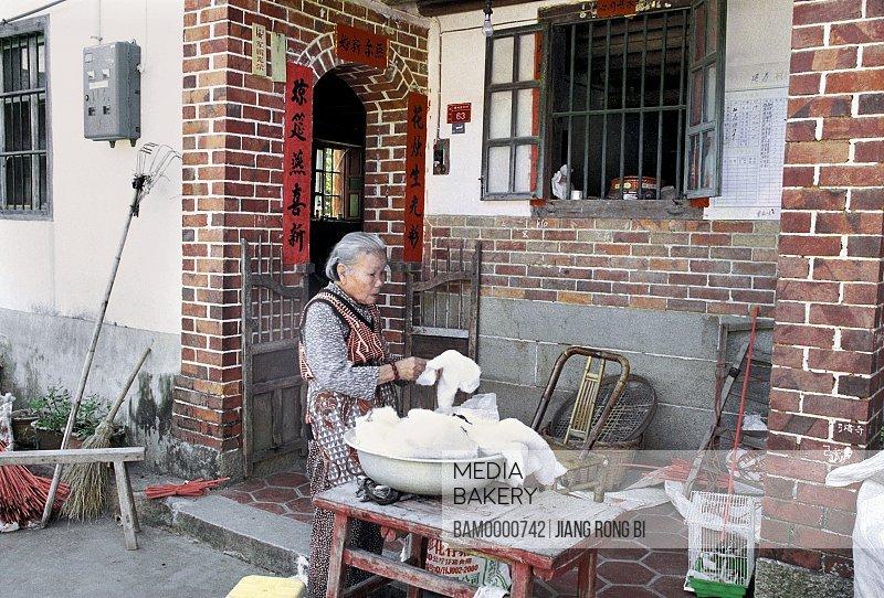 View of senior woman cleaning cotton, Elders from Yanshou Village, Chengxian District, Putian City, Fujian Province, People's Republic of China