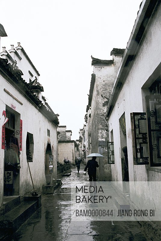 People walking through alleyway in Ancient Xidi Village, Yixian County, Anhui Province, People's Republic of China