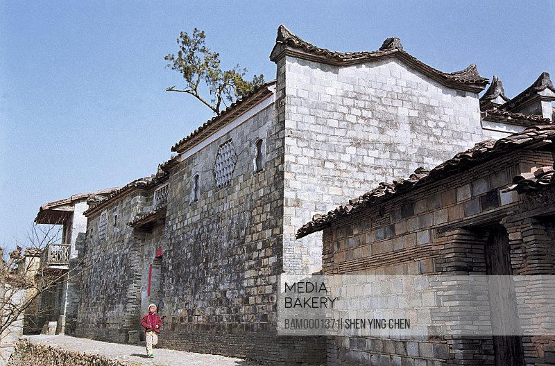 View of a boy running by houses, Ancient common people residence of Ming and Qing Dynasty at old Heping town in Shaowu, Heping town, Shaowu County, Fujian Province of People's Republic of China