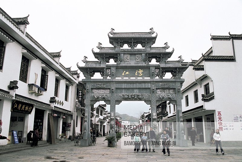 People walking by structures with curved roof, The old town scenery in Jiangwan, Wuyuan County, Jiangxi Province, People's Republic of China