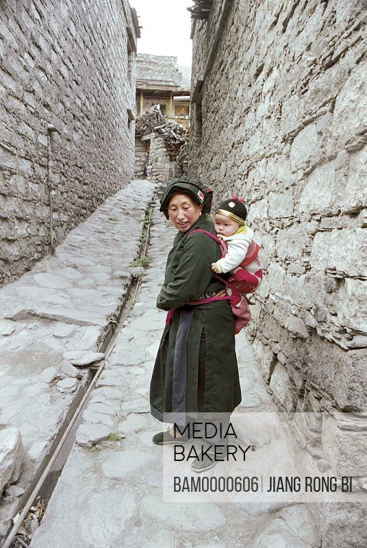 View of a mother piggybacking her baby, The Zang minority woman with the baby on their back in Ganbao Zang minority village, Li County, Aba State, Sichuan Province of People's Republic of China