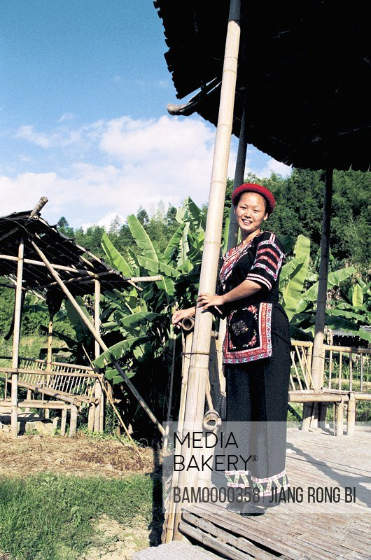 Portrait of a young woman standing under a shelter, She minority village in Rixi township, Fuzhou City, Fujian Province, People's Republic of China