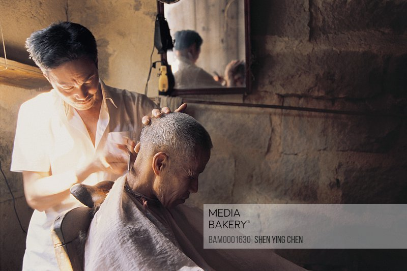 Barber cutting mature man's hair, The wharf Village barber, Luoyuan County, Fujian Province of People's Republic of China