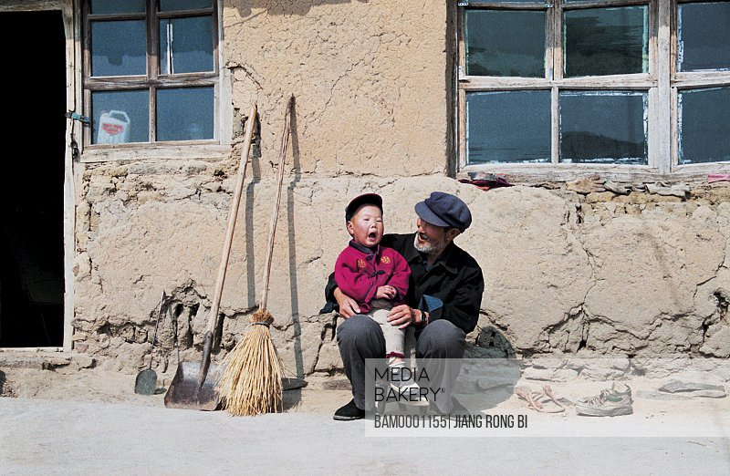 Grandfather sitting with grandson outside house, Peasant family are in sunshine, Guyuan County, Hebei Province of People's Republic of China