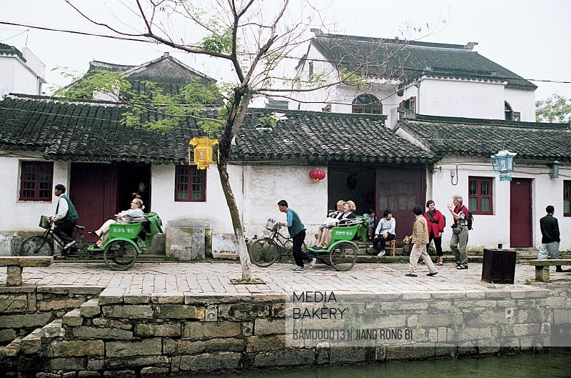 View of people walking by houses, The street of Tongli region of rivers and lakes pond, Tongli Town, Wujiang City, Jiangsu Province of People's Republic of China