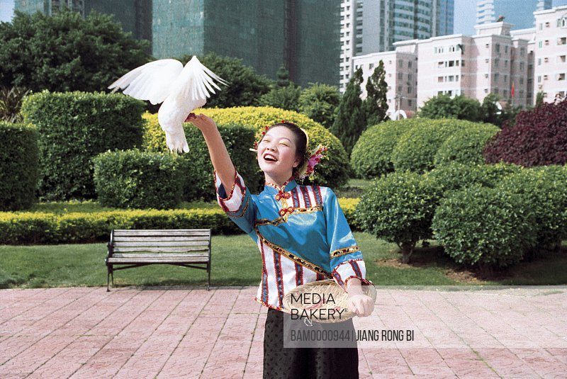 View of a cheerful girl playing with pigeon, Xunpu women at the photographic exhibition often Taiwan strait, Fuzhou City, Fujian Province, People's Republic of China