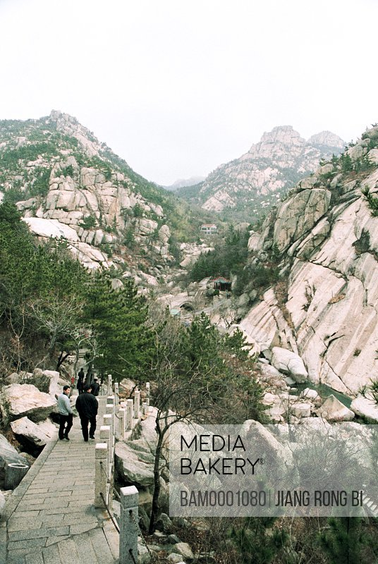 Tourist walking on bridge with mountains in the background, The scenery of Lao Mountain, Qingdao City, Shandong Province of People's Republic of China