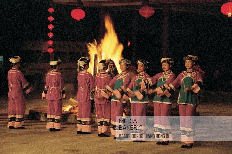 Female dancers dancing by campfire, The campfire evening party in the Miao minority housing of Dehang, Jishou City, Xiangxi Prefecture, Hunan Province, People's Republic of China