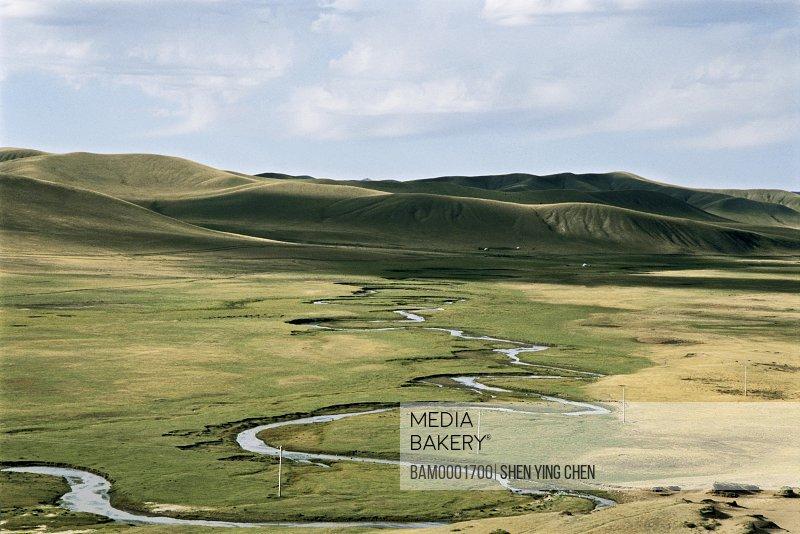 Elevated view of meandering stream passing through grassland, Scenery of the Bayangaole Prairie, Keshiketengqi, Chifeng City, Inner Mongolia Autonomous Region of People's Republic of China