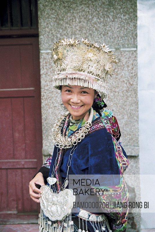 Portrait of cheerful young woman wearing Miao minority dress, Thousand of Miao minority's house of Xijiang, Kaili City, Guizhou Province of People's Republic of China