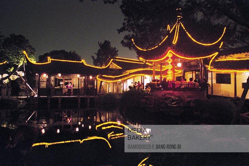 Tourists sitting under illuminated Stupa at night, Wangshi park's night scenery of song dynasty, Suzhou City, Jiangsu Province, People's Republic of China