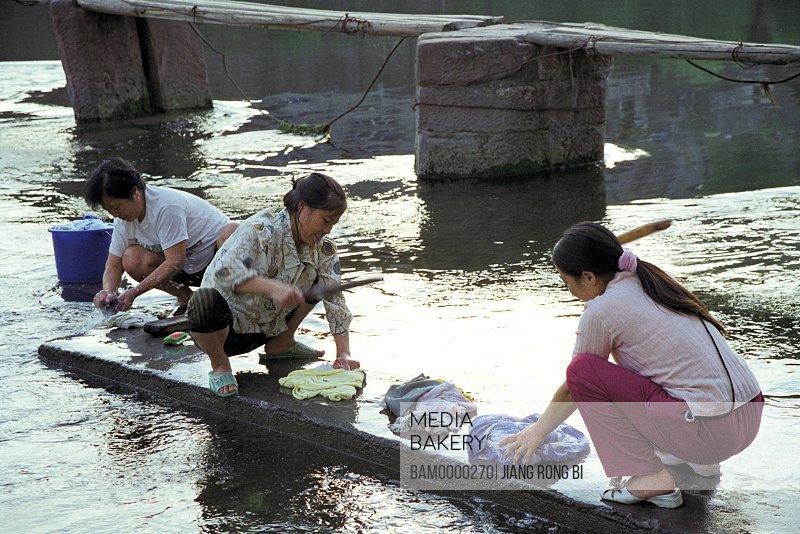 Women washing clothes near riverbank, The washing women near the bank of Tuo River, Fenghuang, Xiangxi Prefecture, Hunan Province, People's Republic of China