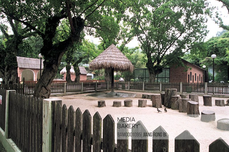 Thatched structure by logs with fence, Shipai Bay Park in Macao, Macao special administration region of People's Republic of China