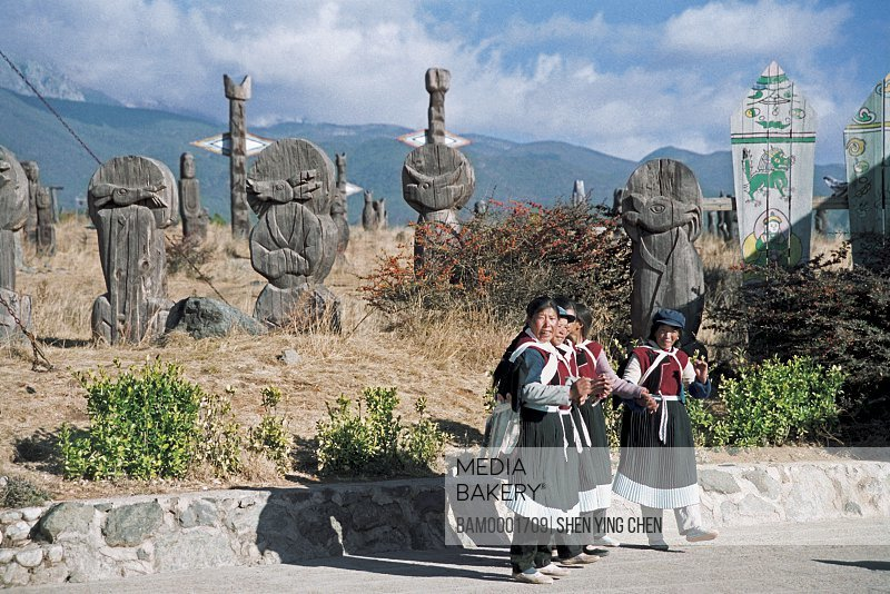 Mature women standing with sculptures in the background, Naxi nationality woman of Dongba God Gardon , Dongba Village, Lijiang City, Yunnan Province of People's Republic of China