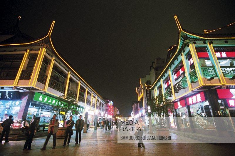 People walking on street amid illuminated buildings at night, The night scenery of Walk-street in Suzhou, Suzhou City, Jiangsu Province, People's Republic of China