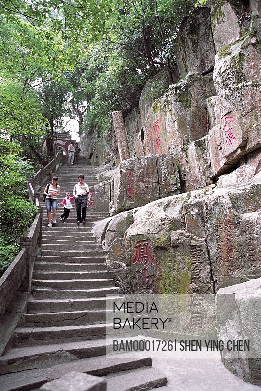 View of people climbing stairs by rock inscription carved on a cliff, Heshui rock inscription carved on a cliff face in Yongquan Temple, Gushan, Fuzhou City, Fujian Province of People's Republic of China