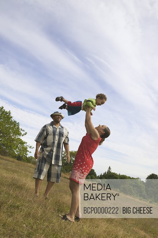 A couple playing with their son in grassy field.