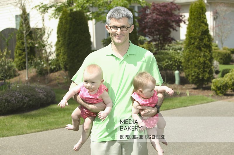 A father holding his two babies outdoors.