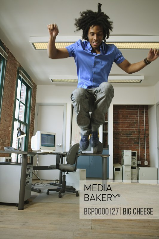 A young man leaping high in the air in a loft-style office.