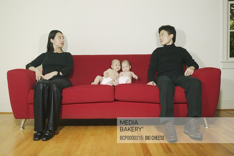 Parents sitting on a sofa with twin babies.