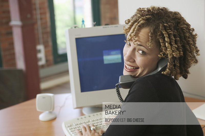 A young woman working at her desk.