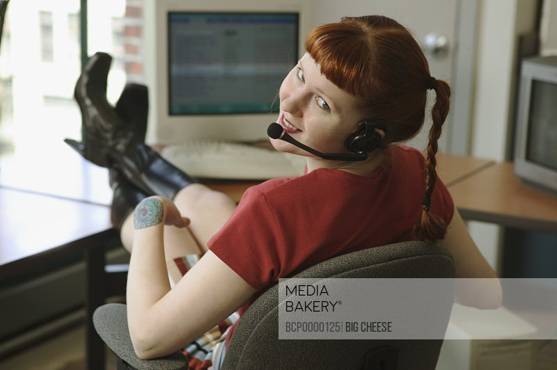 Red-headed woman talking on a headset phone with feet on desk.